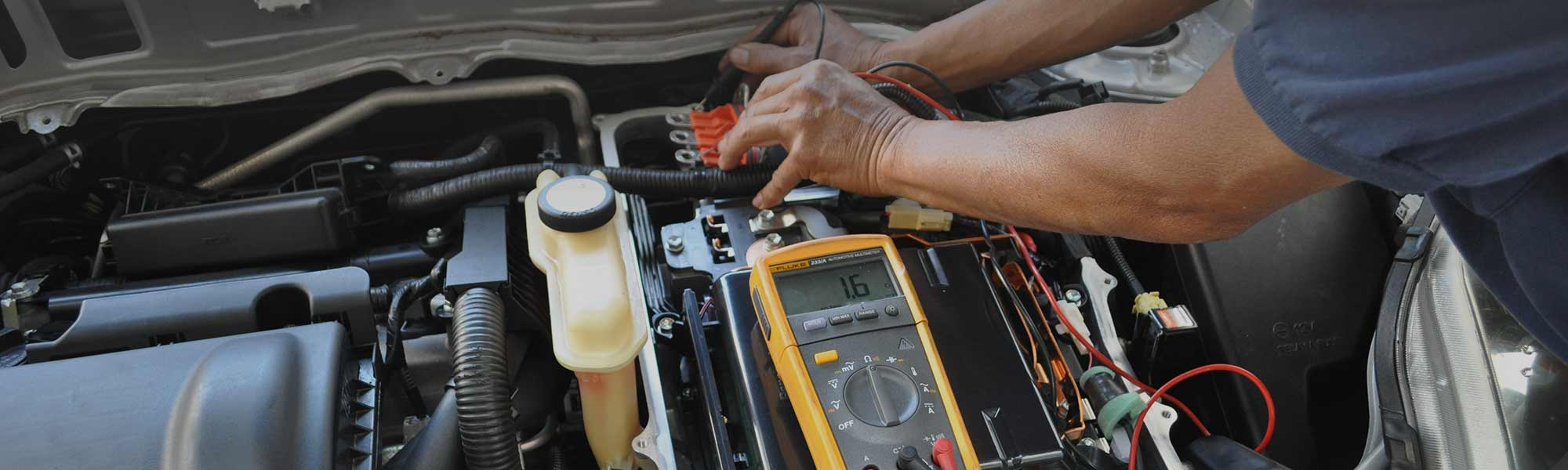 image of mechanic repairing hybrid car motor